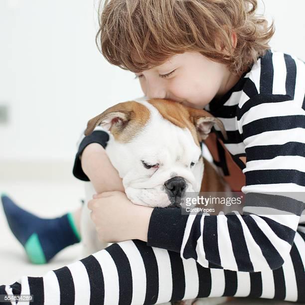 Boy hugging his bulldog