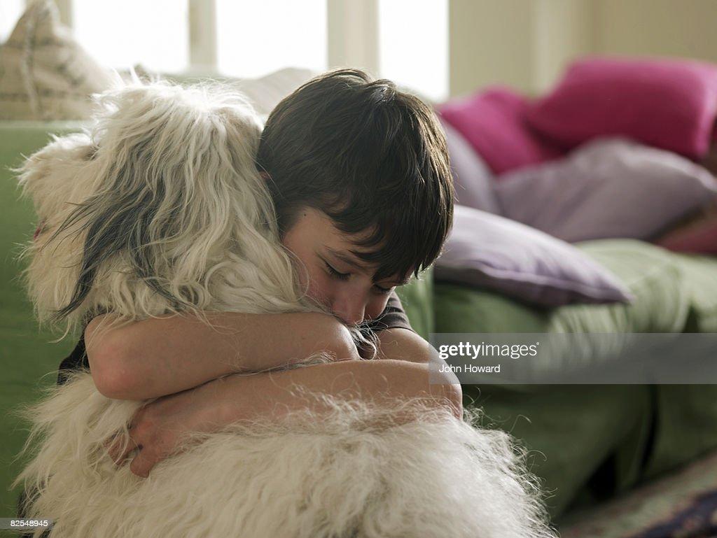 Boy hugging his dog : Stock Photo