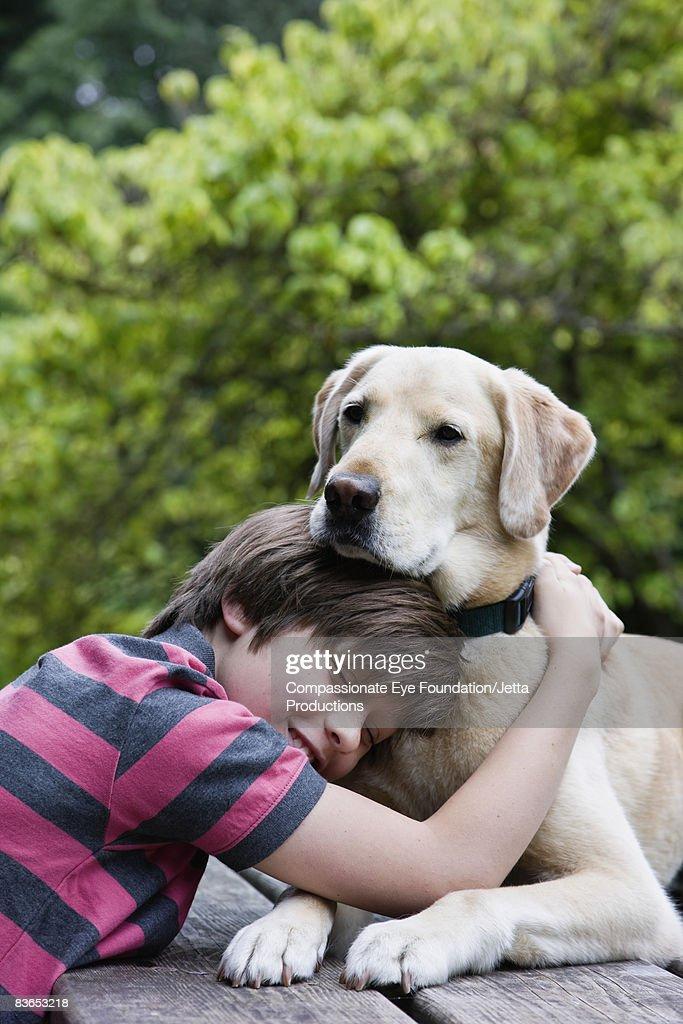 Boy hugging his dog : Stock-Foto