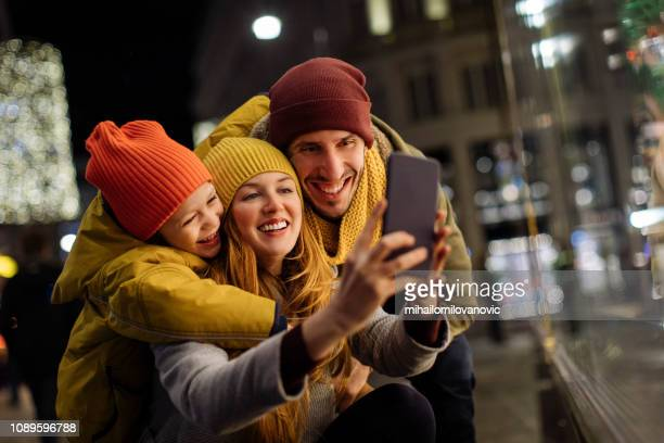 Boy hugging his parents and taking selfie