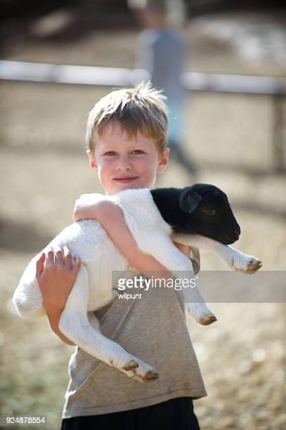 Boy Hugging Lamb Closely