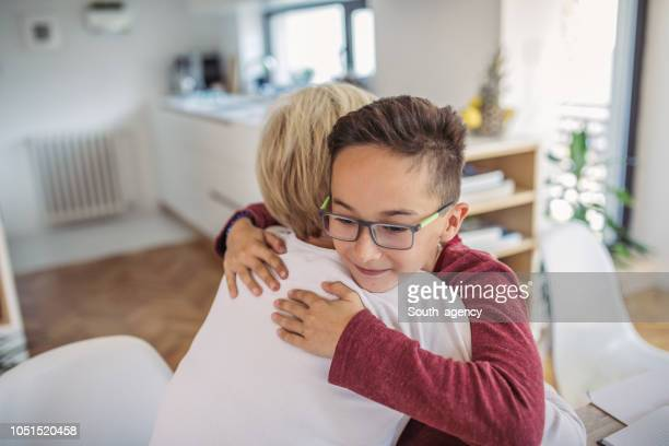 boy hugging mom - child prodigy stock pictures, royalty-free photos & images