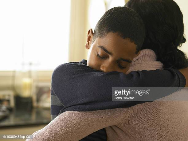 boy (12-13) hugging mother at home - mother and son stock photos and pictures