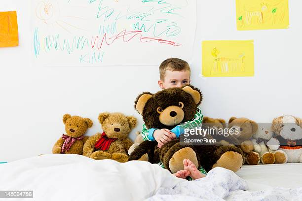 Boy hugging teddy bear on bed