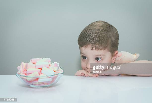 Boy hugging toy, looking at bowl of marshmallows