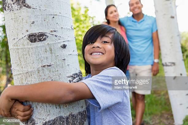 Boy hugging tree outdoors