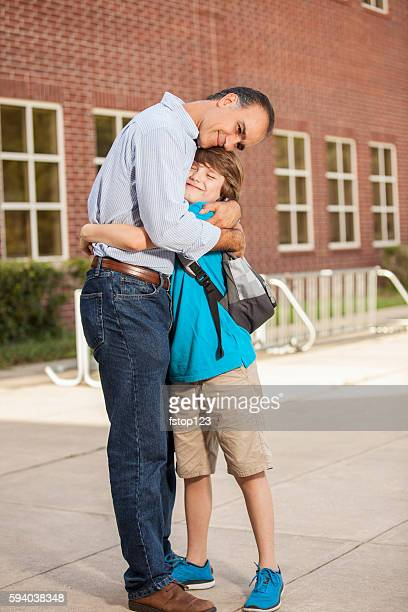 Boy hugs dad goodbye on first day of school.