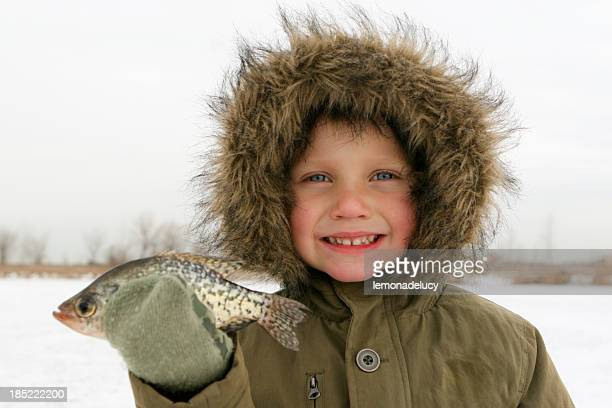 boy ice fishing holds fish - crappie stock pictures, royalty-free photos & images
