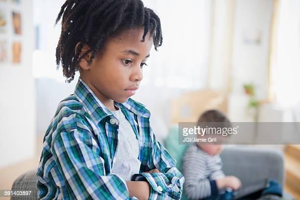 Boy ignoring friend in living room