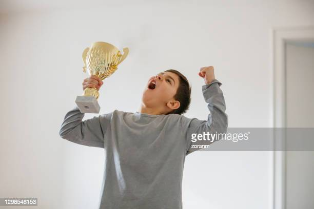 boy imagining success, raising arms with golden trophy and shouting - holding trophy stock pictures, royalty-free photos & images