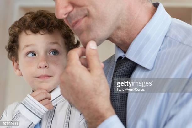 boy imitating his father - hand on chin stock pictures, royalty-free photos & images
