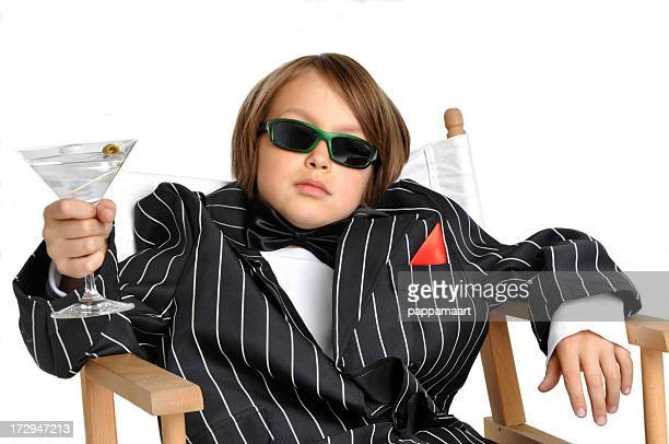 Boy impersonating mister Bond or gangster with Martini