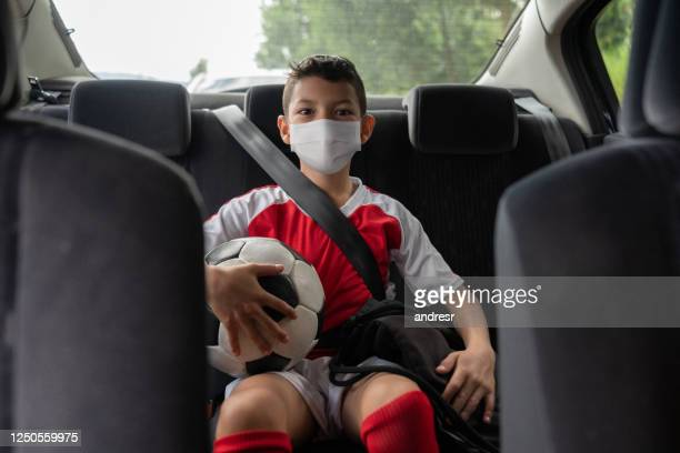 boy in a car on his way to soccer practice wearing a facemask to avoid the coronavirus pandemic - sports training camp stock pictures, royalty-free photos & images