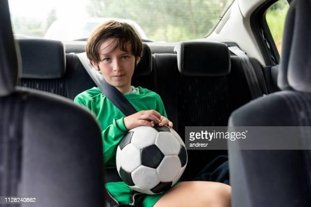 ragazzo in auto a casa dopo allenamento di calcio - divisa sportiva foto e immagini stock