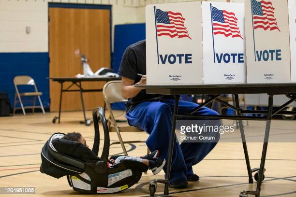 A boy in a child carrier looks at his father as he casts his ballot for the Democratic presidential primary election at a polling place in Armstrong...
