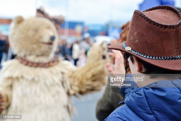 boy in a cowboy hat watching a carnival parade. person disguised as a bear. - bear suit stock pictures, royalty-free photos & images