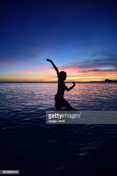 a boy in a cricket bowling action silhouetted against the sunset in palawan island - beach cricket stock pictures, royalty-free photos & images