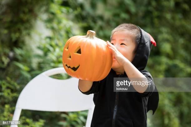 a boy in a devil's clothes has jack - o - rantern. - ghost player foto e immagini stock