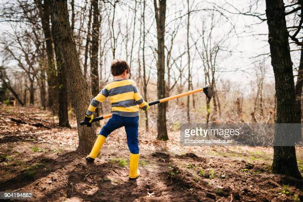 Boy in a garden digging soil with a hoe