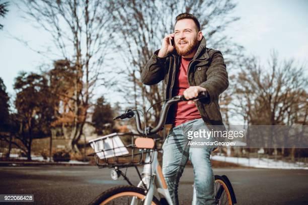 garçon dans une hâte ride une bicyclette et parler sur un téléphone sur une journée d'hiver - froid humour photos et images de collection
