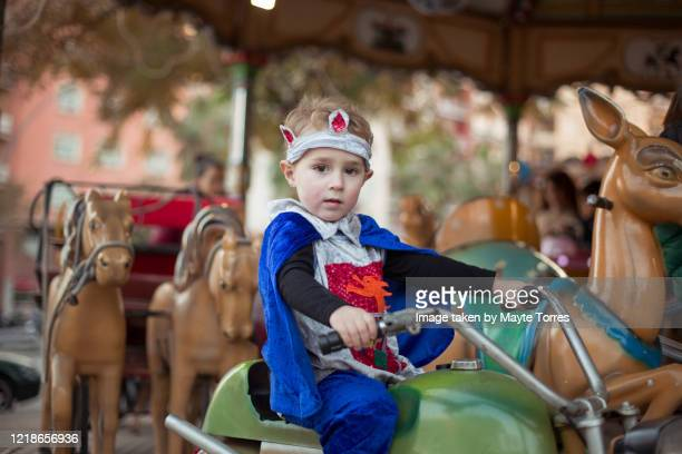 boy in a motorbike at the carousel dressed as a prince - reality kings stock pictures, royalty-free photos & images