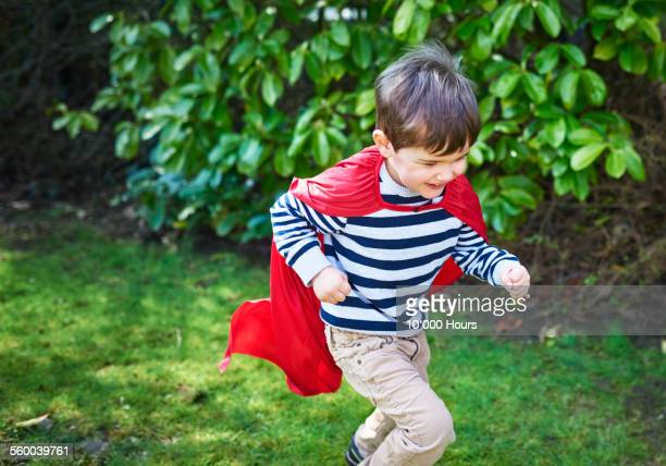 A boy in a red cape playing in the garden