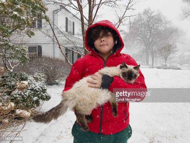 boy in a red coat and holding a cat in the snow - froid humour photos et images de collection