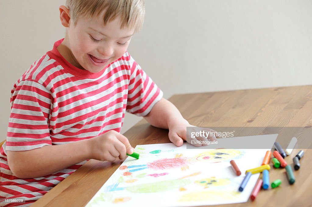 A boy in a red stripes t-shirt coloring with crayons : Stock Photo