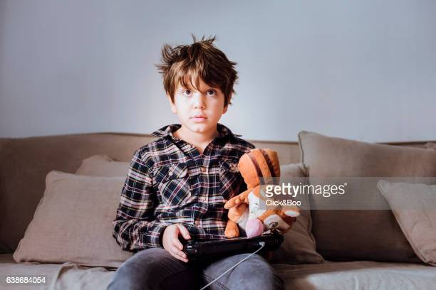 Boy in a sofa playing video games.