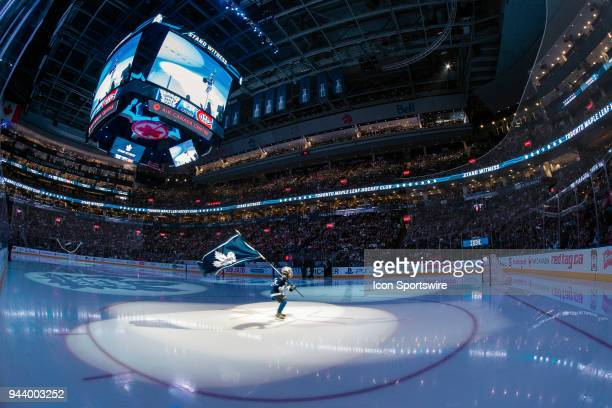 A boy in a Toronto Maple Leaf's uniform carrying a Leaf's flag skates with a spotlight following him before the final NHL 2018 regularseason game...