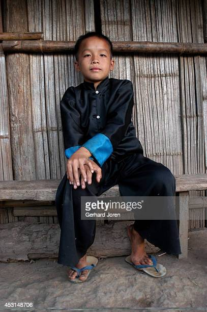 A boy in a traditional Hmong dress sits on a bench in Hoykhe Village with 42 houses and 32 Hmong inhabitants The village on the Mekong River 50 km...