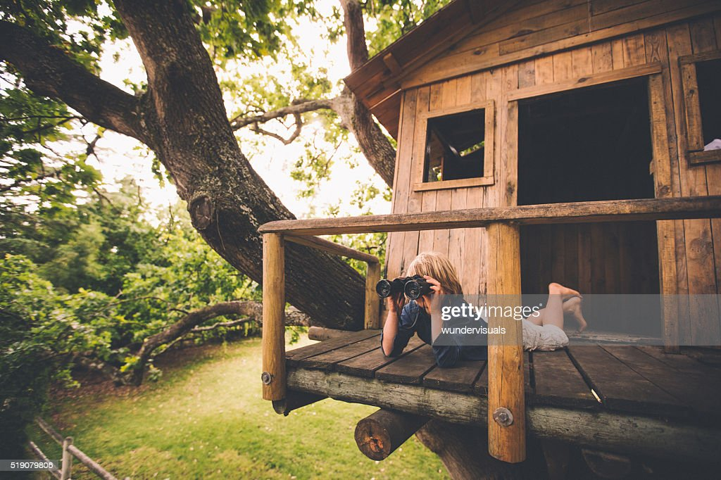 Boy in a treehouse looking in the distance with binoculars : Stock Photo