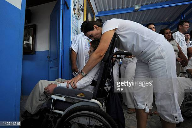 A boy in a wheelchair is driven into Joao de Deus office at the 'Casa de Dom Inacio de Loyola' in Abadiania 120km southwest of Brasilia state of...