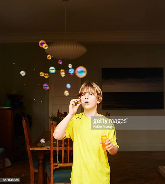 A boy in a yellow shirt blows bubbles at home