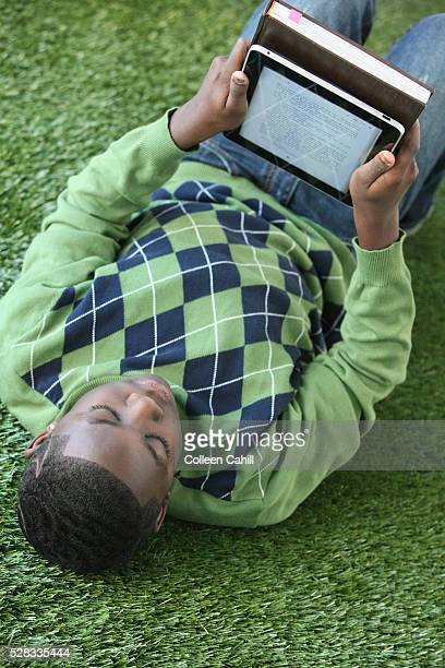 A boy in an argyle sweater lays on the grass reading from an electronic notebook; portland oregon united states of america