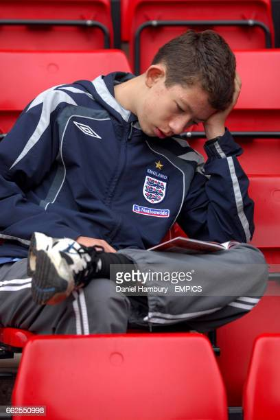 A boy in an England tracksuit reads the match programme in the stands