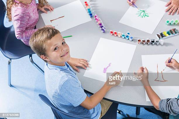 Boy in art class smiling at camera