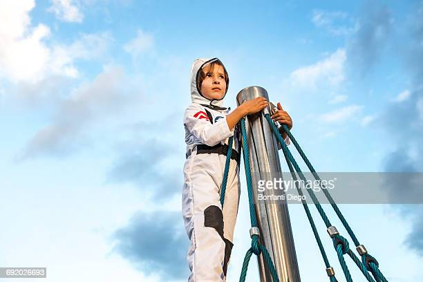 boy in astronaut costume looking out from top of climbing frame - out of frame stock pictures, royalty-free photos & images