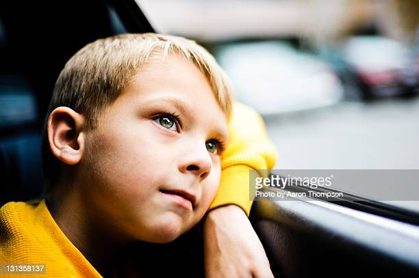 Boy in backseat of car