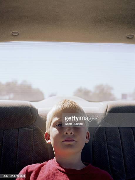 Boy (8-10) in backseat of car, portrait