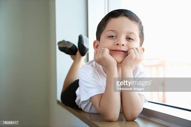 Boy in ballet class lying in window sill