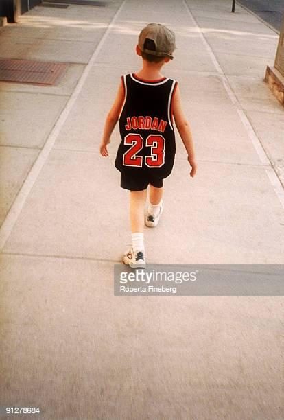 boy in basketball jersey - sporttrui stockfoto's en -beelden
