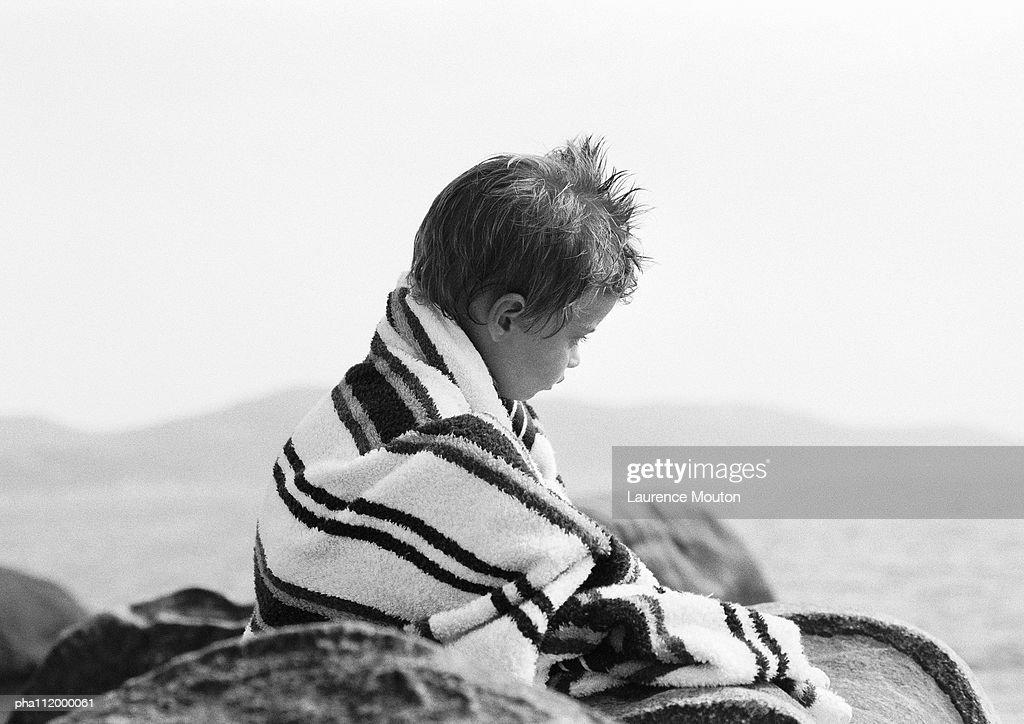 Boy in bath towel, sitting, b&w : Stockfoto