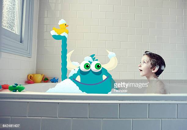 Boy in bath with a monster and yellow duck