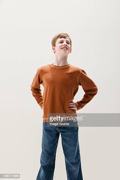 Boy in brown sweater in superhero stance, studio shot