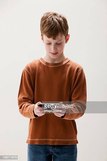 Boy in brown sweater playing hand held video game, studio shot