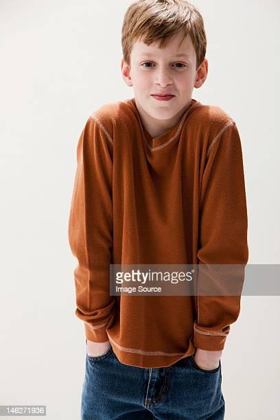 boy in brown sweater with hands in pockets, studio shot - encogerse de hombros fotografías e imágenes de stock