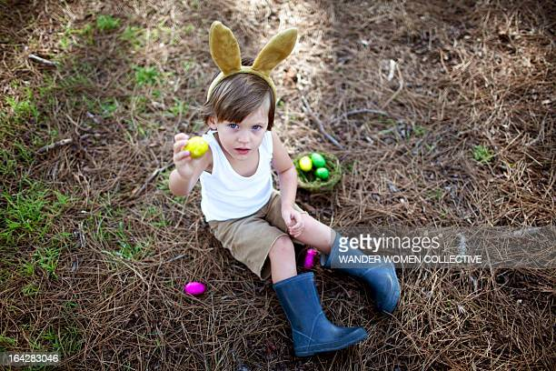 Boy in bunny ears showing Easter Eggs in forest