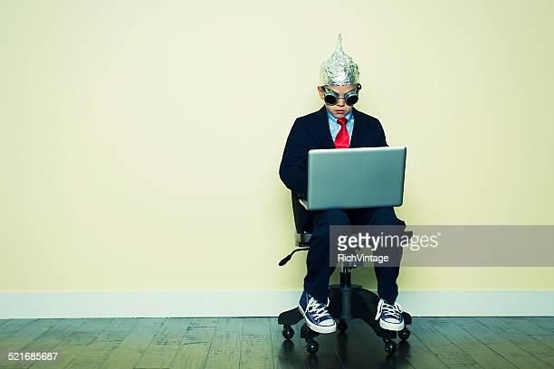 Junge im Business-Anzug sitzt auf Stuhl mit Laptop