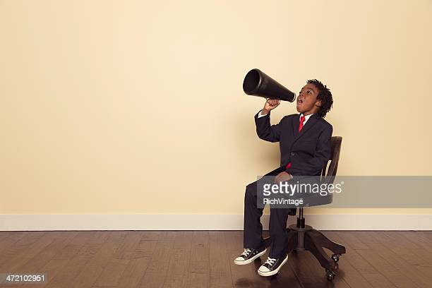 Boy in Business Suit Sitting on Chair Yells through Megaphone